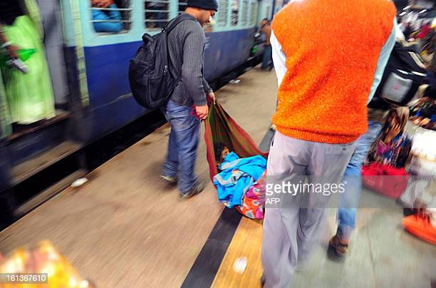 Men carry the body of one of the victims that died during a stampede at the main train station in Allahabad on February 10 2013 At least 10 people...