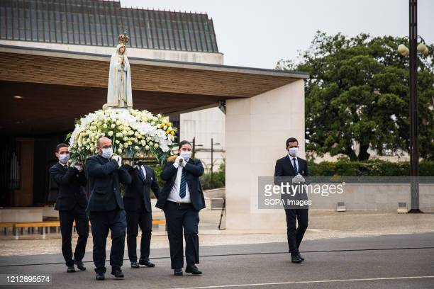 Men carry the figure of Our Lady of Fatima, during the procession. Due to the COVID-19 pandemic, this year's ceremonies are closed to pilgrims, with...