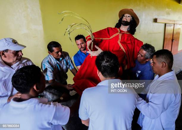 Men carry the image of Jesus Christ before Palm Sunday mass at the Cathedral of Managua on March 25 2018 Palm Sunday marks the beginning of Holy Week...