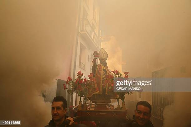 Men carry the statue of San Andres saint patron of the northern Spanish village of Arnedillo as bonfires burn on November 29 in the northern Spanish...