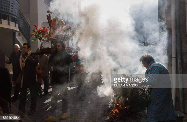 TOPSHOT Men carry the statue of San Andres saint patron of the northern Spanish village of Arnedillo as bonfires burn on November 26 in Arnedillo...