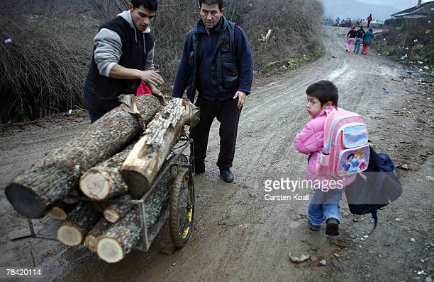 Men carry wood for heating on their way to the Cesmin Lug refugee camp in the Serbian district December 11 2007 in Kosovo province Serbia One hundred...