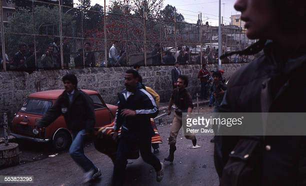 Men carrying a makeshift stretcher run on the streets amid the destruction and damage at the scene of the suicide bombing of the American Embassy,...