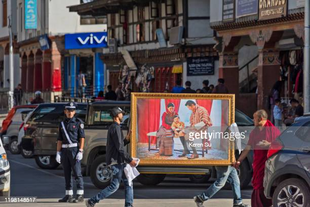 men carrying a painting of the king's family on the street, thimphu, bhutan - thimphu stock pictures, royalty-free photos & images