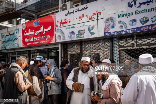 Men carrying bundles of cash stand outside foreign exchange stores at the money exchange market in Kabul Afghanistan on Thursday July 12 2018 US...