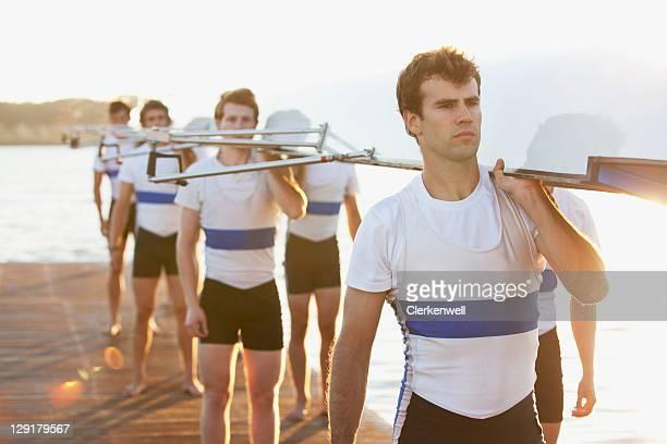 männer tragen kanu auf den schultern - mannschaftssport stock-fotos und bilder