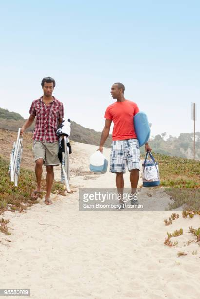 Men carrying cooler, chairs and bags to beach