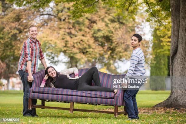 Men carrying friend on sofa in park