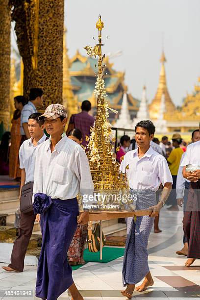 men carrying golden spire to temple - merten snijders - fotografias e filmes do acervo