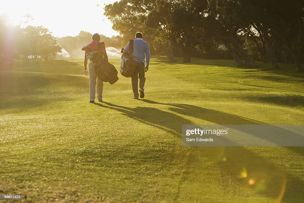 Men carrying golf bags on golf course : Stock Photo
