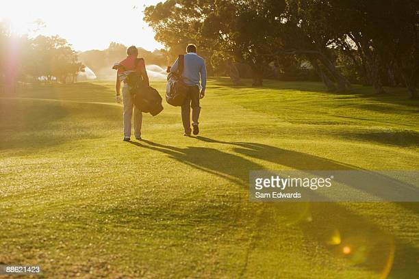 Men carrying golf bags on golf course