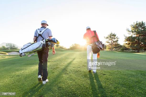 men carrying golf bags on sunny golf course - golfe imagens e fotografias de stock