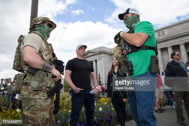 Men carrying guns gather with hundreds of others at a 'Hazardous Liberty! Defend the Constitution!' rally to protest the stay-at-home order, at the...