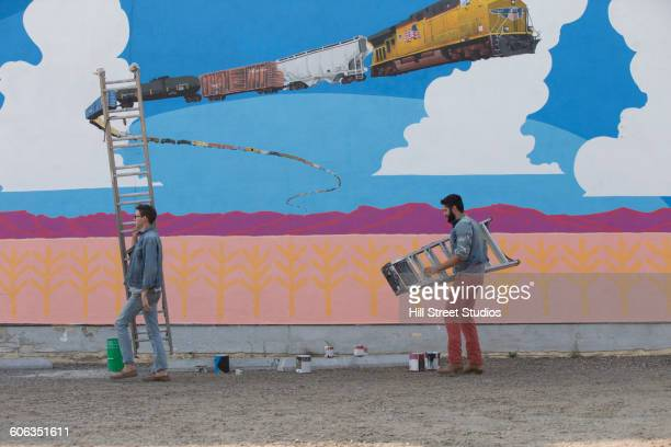 Men carrying ladders at mural wall