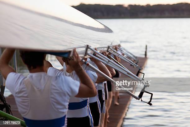 Men carrying long canoe over hear