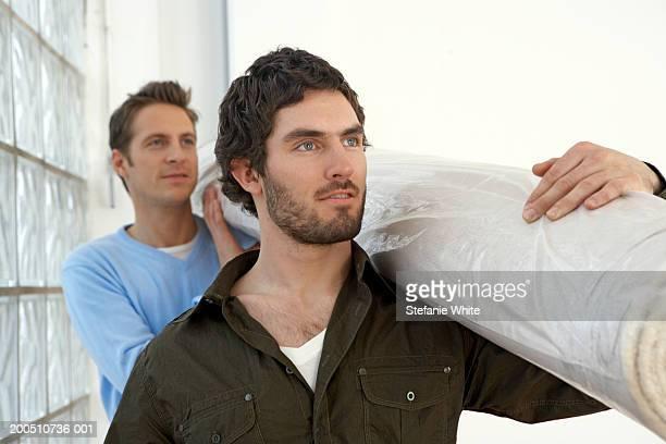 Men carrying rolled up carpet on shoulders