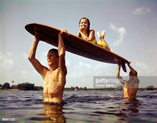 Men carrying woman on surfboard in ocean