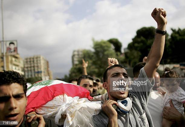 Men chant anti-Israeli slogans while carrying a body during a mass funeral August 9, 2006 in Beirut, Lebanon. The funeral was held for people...