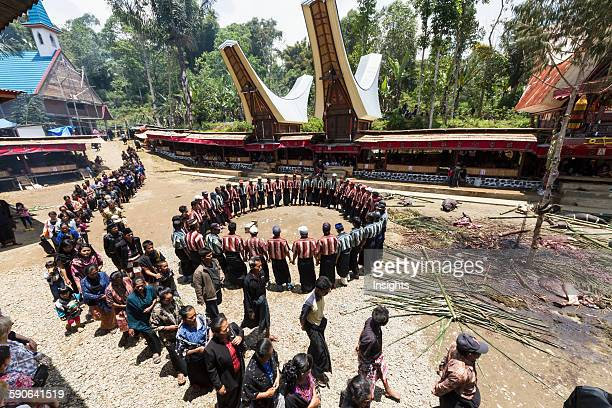 Men chanting in a circle and people in a formal funeral procession called Ma'passa Tedong at a rante the ceremonial site for a Torajan funeral in...