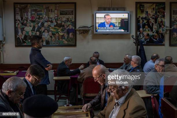 Men chat and drink chai at a teahouse while footage of Turkish President Recep Tayyip Erdogan after casting his referendum vote is seen on a tv on...