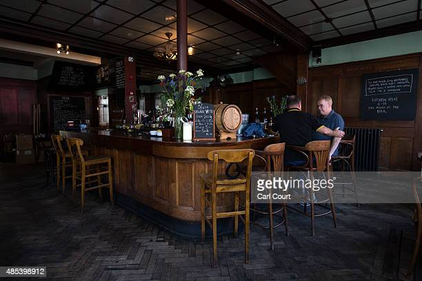 Men chat at the bar in the Royal Oak pub on Columbia Road on August 27 2015 in London England The Royal Oak pub was named as one of 21 interwar pubs...