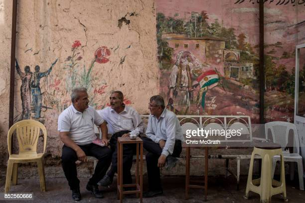 Men chat in front of a Kurdish mural ahead of the upcoming referendum for independence of Kurdistan on September 23 2017 in Sulaymaniyah Iraq The...