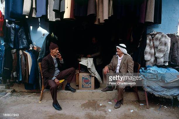 Men chat outside a clothes shop in a war torn street in the Shatilla Palestinian refugee camp during the civil war