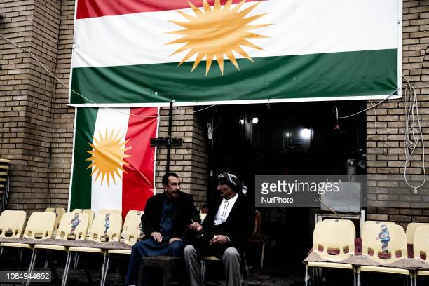 Men chatting surrounded by Kurdish flag in Irbil city center On December 2018 A trip inside Kurdistan between Irbil and Sulaymaniyya a Country that...