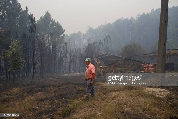 Men check a burned house after a wildfire took dozens of lives on June 19 2017 near Castanheira de Pera in Leiria district Portugal On Saturday night...