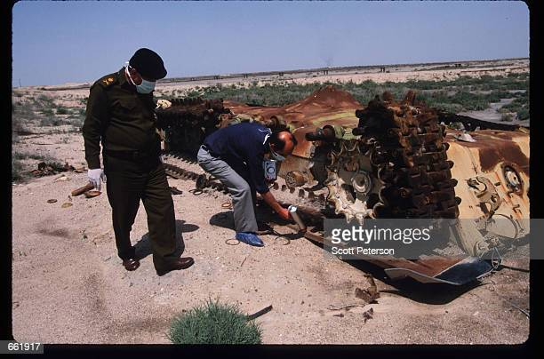 Men check an abandoned Iraqi tank for radiation levels May 1 1998 in Basra Iraq Depleted uranium was used extensively by UN troops during the Gulf...