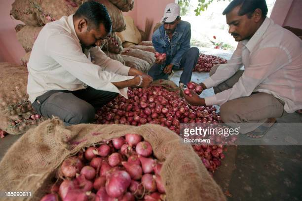 Men check onions at a wholesale market in Nashik Maharashtra India on Wednesday Oct 23 2013 Onion prices in India may extend a record rally as heavy...