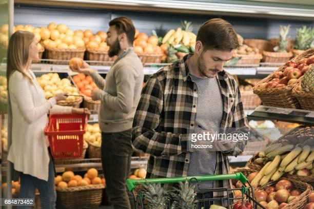 Hommes, vérification de la liste d'achats à la section des fruits au supermarché