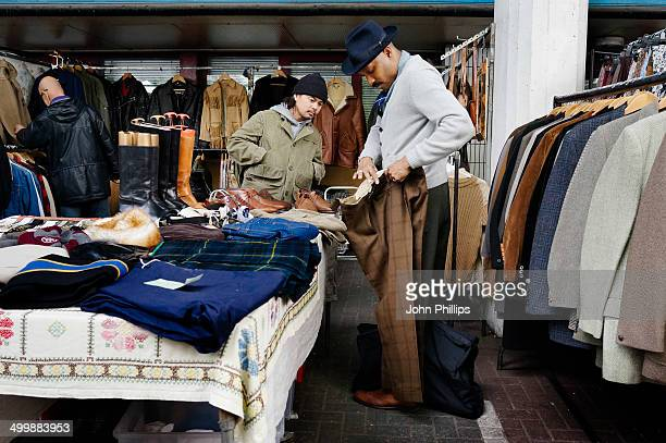 Men choosing clothes at a stall in London's Portobello Road market.