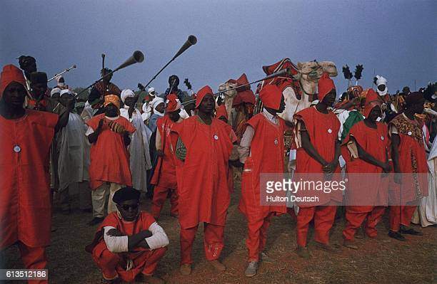 Men clad in bright tunics and hoods and musicians playing traditional Hausa instruments provide a welcoming committee for Queen Elizabeth II during...