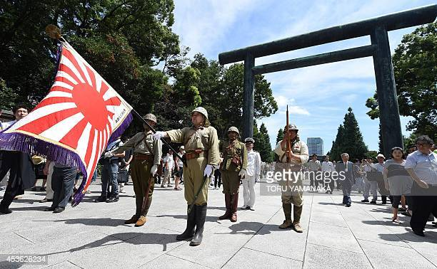 Men clad in Japanese Imperial Army and Navy uniforms stand at attention at the entrance to the controversial Yasukuni shrine as people visit to offer...