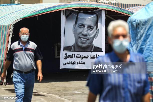 Men clad in masks due to the COVDI-19 coronavirus pandemic walk past a mourning tent bearing the poster of slain Iraqi jihadism expert Hisham...