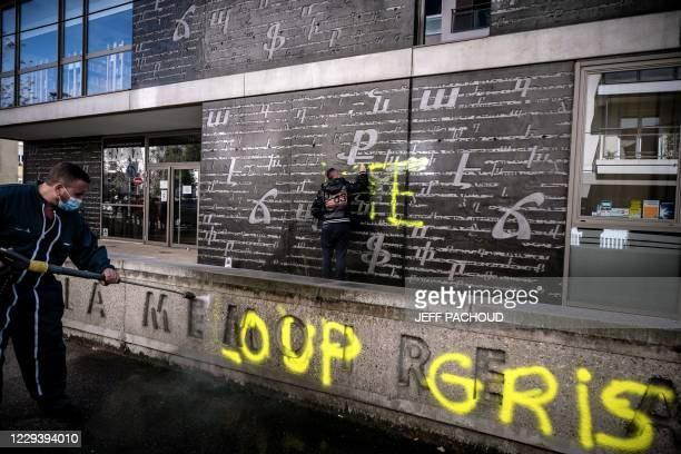 Men clean an outside wall of the National Armenian Memorial Centre in Decines-Charpieu, near Lyon, on November 1, 2020 where pro-Turkish yellow...