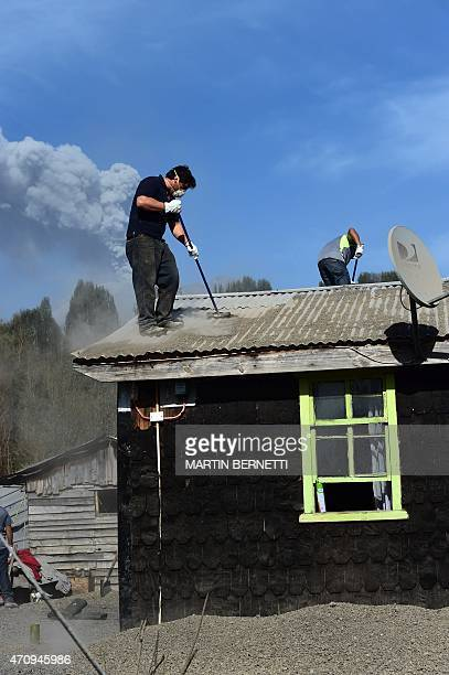 Men clean the roof of a house in La Ensenada, Chile with the Calbuco volcano in the background, on April 24, 2015. Southern Chile remained on alert...