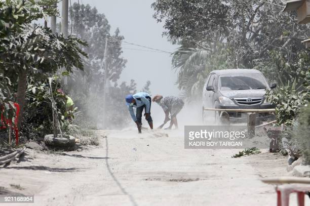TOPSHOT Men clean volcanic ash from the street after Mount Sinabung volcano spewed thick volcanic ash across the area the day before in Karo North...