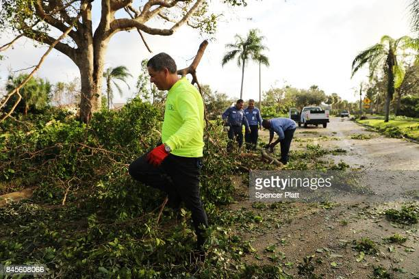 Men clear debris from a roadway the morning after Hurricane Irma swept through the area on September 11 2017 in Naples Florida Hurricane Irma made...