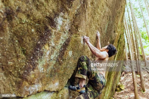 Männer, die einen großen Felsen klettern