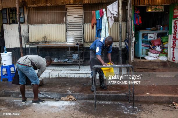 Men closes shop before the beginning of a curfew which was ordered by Kenyan President, Uhuru Kenyatta, to contain the spread of the COVID-19...