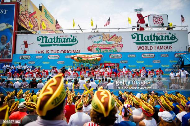 Men compete during the annual Nathan's Hot Dog Eating Contest on July 4 2018 in the Coney Island neighborhood of the Brooklyn borough of New York...