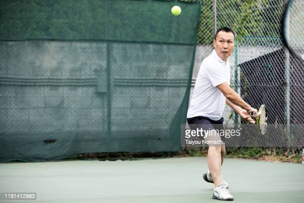men concentrating on tennis practice - テニスラケット ストックフォトと画像