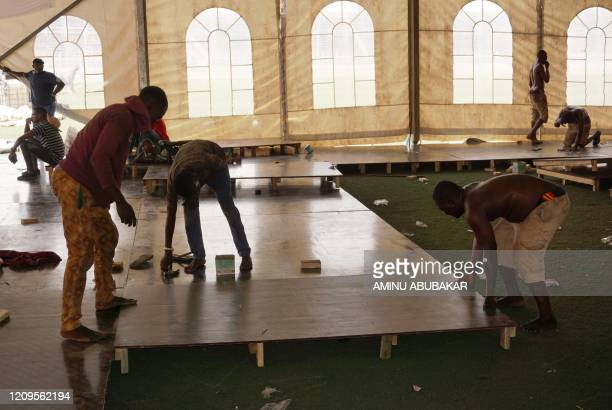 Men construct wooden flooring at a COVID-19 coronavirus isolation centre at the Sani Abacha stadium in Kano, Nigeria, on April 7, 2020. - The centre...