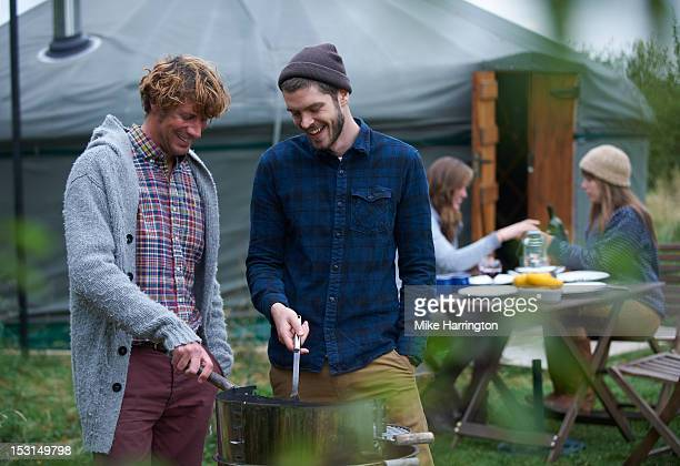 Men conversing over barbecue on glamping holiday.