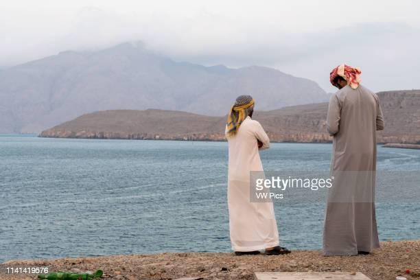 Men conversing while overlooking the Musandam peninsula Khasab Oman