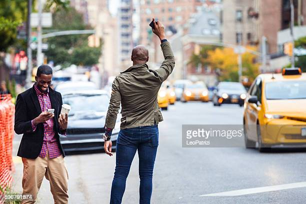 men couple hailing a taxi in new york - hail stock pictures, royalty-free photos & images
