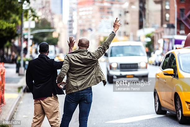Men couple hailing a taxi in New York
