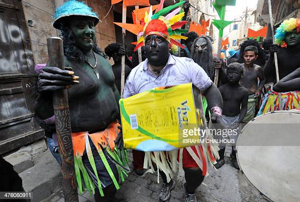 Men covered in black body paint and dressed up parade in a street during the annual festival of Zambo that celebrates the beginning of lent the...